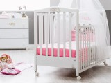 Lettino prima infanzia bianco della linea Hello di Italbaby su ruote piroettanti con cassetto sotto rete a doghe e con kit tessile disponibile rosa o azzurro